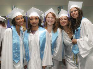 Image shows 4 WCU graduates smiling after graduation