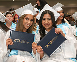 Two WCUI graduates holding up their diplomas smiling