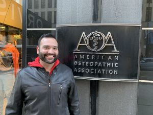 Picture of Dr. Matwick's son standing in front of the American Osteopathic Association sign and smiling