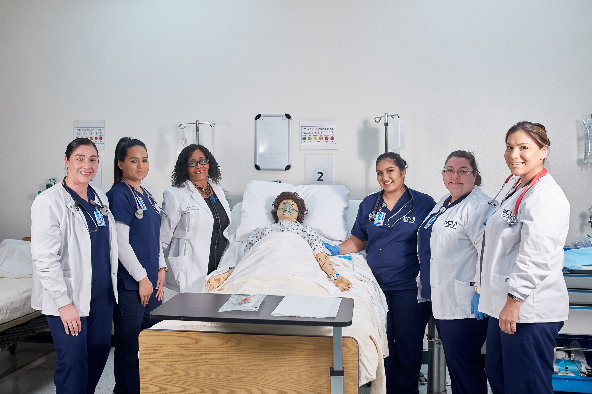 WCUI nurses and an instructor smiling in a nursing lab around a mock patient